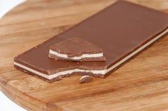 Bruten brun vit choklad på träbrädet Royaltyfri Foto