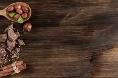 Bruten chokladstång, hasselnöt och kanel på träbakgrund Arkivfoton