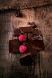 Bruten chokladstång med röda mogna hallon på mörk brunt b Royaltyfri Fotografi