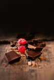 Bruten chokladstång med röda mogna hallon på mörk brunt b Arkivbilder