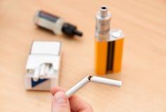 Bruten cigarett vs e-cigaretten Royaltyfria Bilder