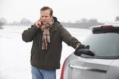 Bruten Down för bilist i snöig landskap royaltyfri foto