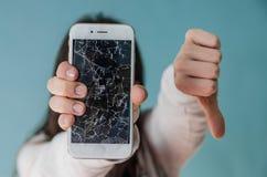 Bruten exponeringsglasskärmsmartphone i hand av den upprivna kvinnan arkivfoto