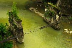 Bruten fot- upphängningbro över bergfloden arkivfoton