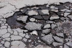 Bruten grop med stycken av asfalt D?lig asfaltv?g r royaltyfri fotografi
