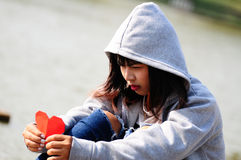 Bruten -hjärtad flicka som ser röd pappers- hjärta royaltyfri foto