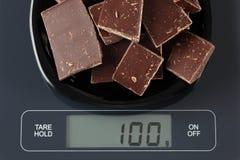 Bruten mörk choklad på kökskala Arkivbild