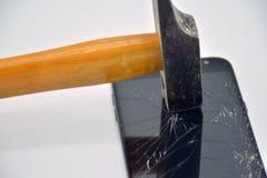 Bruten mobiltelefonsk?rm med en hammare royaltyfria bilder