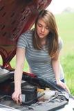 Bruten ner kvinnlig bilist som ser bilmotorn royaltyfri bild