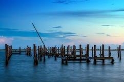 Bruten pir och mast av det brutna skeppet i vatten efter solnedgång Royaltyfri Bild