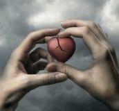 Bruten röd hjärta i händer Royaltyfri Foto