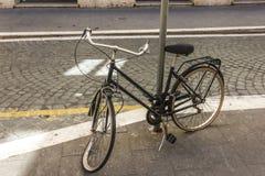 Bruten retro cykel med det deflaterade och skadade hjulet, enchained till den ljusa pelaren i gatan av Rome royaltyfri foto