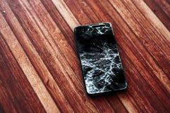 Bruten smartphone med realistiskt splittra av pekskärmen på träbakgrund Arkivbild