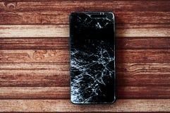 Bruten smartphone med realistiskt splittra av pekskärmen på träbakgrund Royaltyfria Bilder