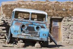 Bruten 4x4 som framme parkeras av lantliga stenar hus, Bolivia Arkivbild