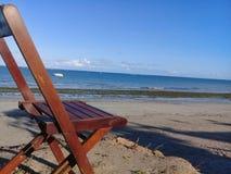 Bruten stol på stranden och ett fartyg bakom arkivbilder