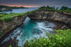 Bruten strand pÃ¥ den Nusa Penida ön pÃ¥ soluppgÃ¥ng fotografering för bildbyråer