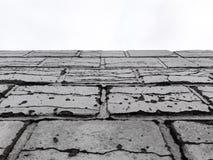 Bruten tegelstenvägg som är svartvit med himmel arkivfoto