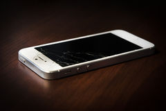 Bruten telefon på en tabell, svart skärm arkivfoton