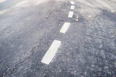 Bruten vit avskiljandelinje på vägen arkivfoto