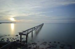 Bruten wood bro och vågor som kraschar på havet på under solnedgången Royaltyfri Bild