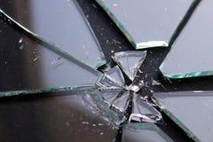 Brutet exponeringsglas med små stycklögner på en svart yttersida royaltyfri foto