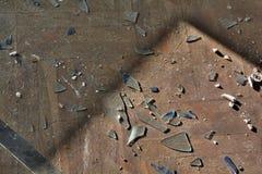 Brutet exponeringsglas på ett golv arkivbilder
