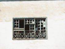 Brutet fönster i gammalt övergivet hus Arkivbild
