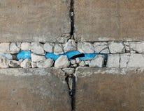 Brutet gammalt blåttpvc-rör under bruten gammal betongjordning arkivbild