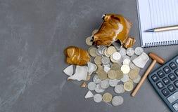 Brutet piggy med räknemaskinen, mynt, penna, anmärkningsbegrepp på tabellen Arkivfoto