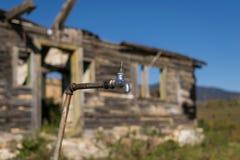 Brutet vattenklapp med övergiven byggande bakgrund Arkivfoton