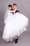 Bräutigam hält Braut im Studio an Stockfoto