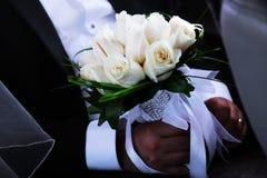 Bräutigam mit einem Blumenstrauß von weißen Rosen Stockbilder