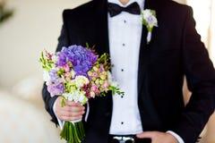 Bräutigam mit schönem Hochzeitsblumenstrauß Stockfotografie