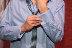 Bräutigam trägt Manschettenknöpfe auf den Ärmeln Lizenzfreie Stockbilder
