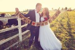 Bräutigam und Braut, die gerade verheiratete Buchstaben halten Stockbild