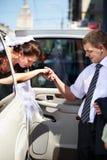 Bräutigam, welche seiner Braut aus Hochzeitslimousine heraus hilft Stockfoto