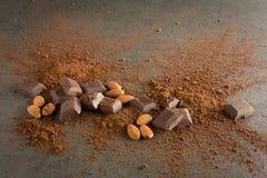 Brutna chokladstycken med den kakaopulver och mandeln på stenlodisar Arkivfoto