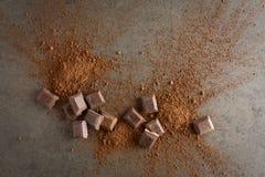 Brutna chokladstycken och kakaopulver på stenbakgrund Royaltyfria Bilder