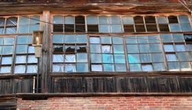 Brutna fönster av ett övergett hus royaltyfri foto