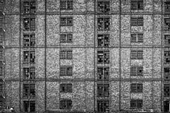 Brutna fönster i enormt övergivet lager Arkivfoto