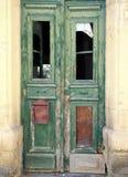 Brutna gamla gröna dörrar i ett övergett övergivet hus med brutna fönster och urblekt skalning målar Royaltyfri Fotografi