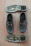 Brutna gamla skor på det smutsiga golvet Arkivfoto