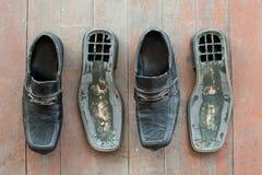 Brutna gamla skor på det smutsiga golvet Royaltyfria Bilder