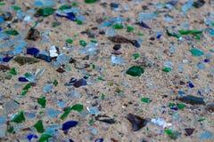 Brutna glasflaskor på vit sand Flaskor är grön och blå färg Avfall på sanden ekologiskt problem royaltyfri foto