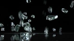 Brutna glass nedgångar till golvet Svart bakgrund långsam rörelse