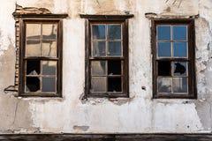 Brutna husfönster arkivbild