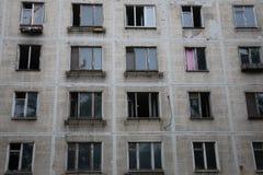 Brutna och öppna fönster i övergiven hyreshus royaltyfria bilder