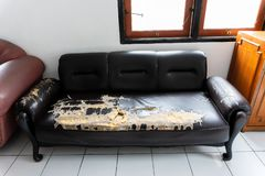 Brutna och gamla bruna soffastolar royaltyfri foto