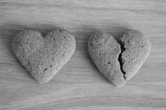 Brutna och obrutna mördegskakahjärtor på träbakgrund som är svartvit som olycklig förälskelsebakgrund Royaltyfri Fotografi